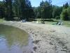 En plan gräsyta följa av en långgrund sandstrand