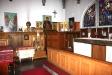 Bakom altaret ett rundbågigt fönster med glasmålning av Einar Forseth.