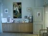 Vacker textil ovanför bokbordet och konstutställning i korridoren till höger