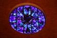 Rundfönstret av Uno Lindberg. I blåfärgat glas med röda prickar.