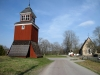 En klockstapel står på andra sidan landsvägen nordväst om kyrkan med årtalet 1758 påmålat.
