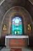 Korfönstret utfördes 1910 i glasmosaik efter ett mönster av Gunnar Hallström.