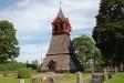 På kyrkogårdens norra del står en klockstapel.