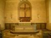 Till höger i koret står en ensam dopfunt i trä