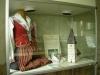 Bjälbodräkten och modell av kyrkan i skåp under läktaren