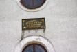 Minnestavla över kyrkan entré.