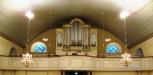 Orgelläktare med sittplatser på båda sidor.