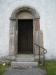 Runsten inmurad i väggen vid portalen