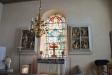 Glasmålningen flankeras av ett delat altarskåp