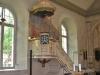 Predikstolen med draperimålning på väggen.