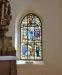 En av två glasmålningar som flankerar altartavlan