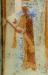 Hialmsvith i elegant röd mantel i blått rutmönster. På huvudet har hon en vit duk.