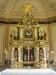 Bakom altaret hänger en klocka
