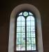 Under orgelläktaren hänger några smidda vindflöjlar