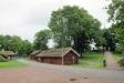Kyrkan väl inbbäddad bland stora träd omgiven av mycket gamla trähus i timmer vid parkeringens entrè