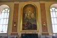 En äldre altartavla hänger på östra väggen