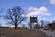 Klockstapeln står på en öppning som kan tolkas lite som en park i det annars täta bostadsområdet