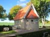 En liten idyllisk byggnad bland högväxta lövträd med välskött kyrkogård.