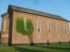 Kyrkan är byggd i samma röda tegel som byggnaderna runt omkring.
