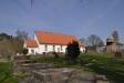 Kyrkan ligger nu omgärdad av köplador på två sidor