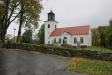 Kyrkans framsida mot huvudingången och parkeringen samt församlingsgården.