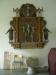 En äldre altaruppsats ovanför dopfunten