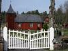 Enkel träkyrka innanför vita grindar