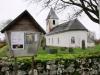 Sörby kyrka informerar besökarna vid en välklädd stenmur av grön mossa.