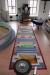 En färgglad vacker matta framför altaret och dopfunten.