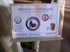 En välkomnande skylt med inbjudan till en mugg kaffe med kaka vid ingångsdörren.