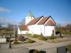 Nyputsad kyrka lyser mycket vit i solskenet. Foto:Bertil Mattsson