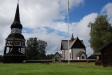 En vacker gammal kyrka med klockstapel och port.